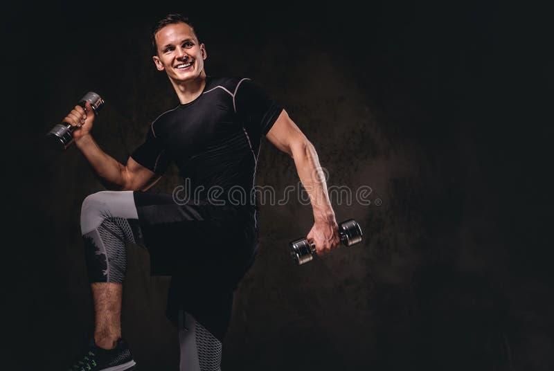 做与哑铃的一件年轻爱好健美者佩带的运动服锻炼在黑暗的背景 库存照片
