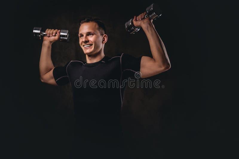 做与哑铃的一件年轻爱好健美者佩带的运动服锻炼在黑暗的背景 免版税库存图片