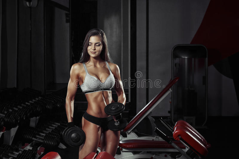 做与哑铃的健身妇女健身锻炼在健身房 图库摄影