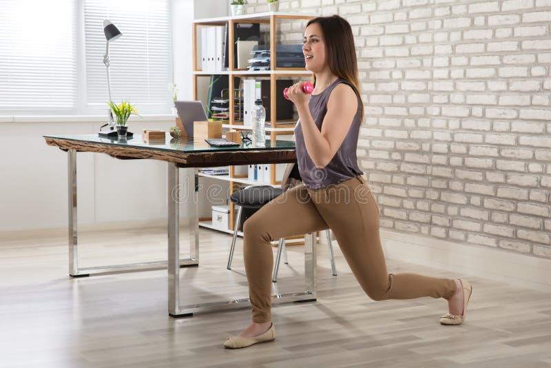 做与哑铃的女实业家锻炼 免版税图库摄影