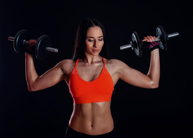 做与哑铃的好性感的女孩锻炼被隔绝在黑背景 运动少妇做与重量的健身锻炼 免版税库存图片