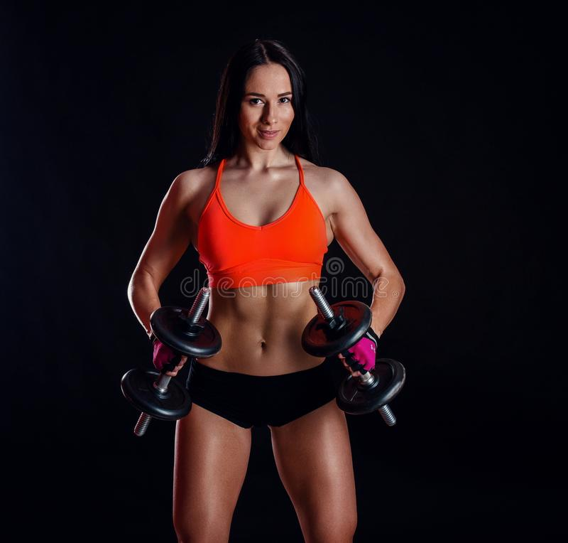 做与哑铃的好性感的女孩锻炼被隔绝在黑背景 运动少妇做与重量的健身锻炼 库存照片