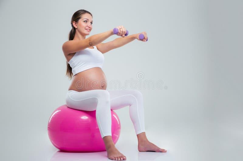 做与哑铃的妇女锻炼在健身球 库存图片