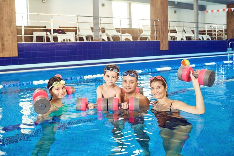 做与哑铃的幸福家庭锻炼在游泳场 库存图片