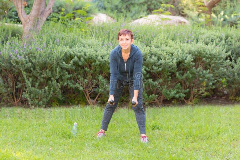 做与哑铃的愉快的微笑的美丽的年长妇女体育锻炼在一个公园在一好日子 库存图片