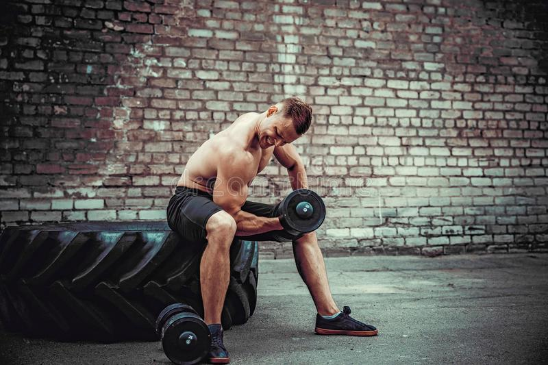 做与哑铃的肌肉人锻炼对砖墙 免版税库存照片