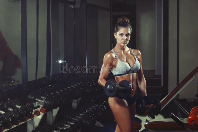 做与哑铃的运动女孩健身锻炼在健身房 免版税图库摄影