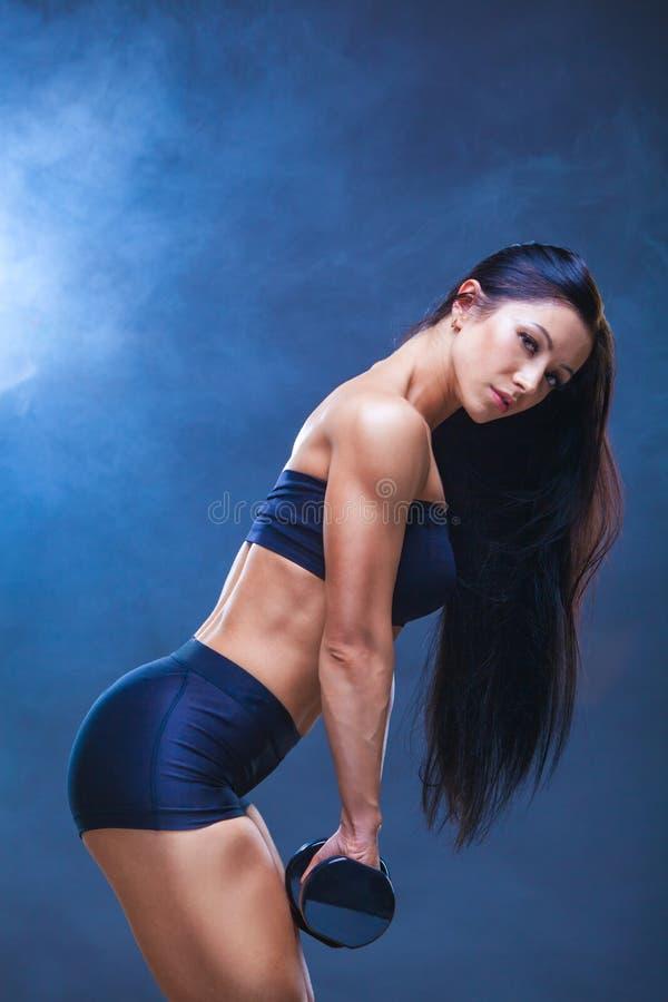做与哑铃的运动少妇健身锻炼在黑演播室背景 在寿衣附近模型 免版税库存图片