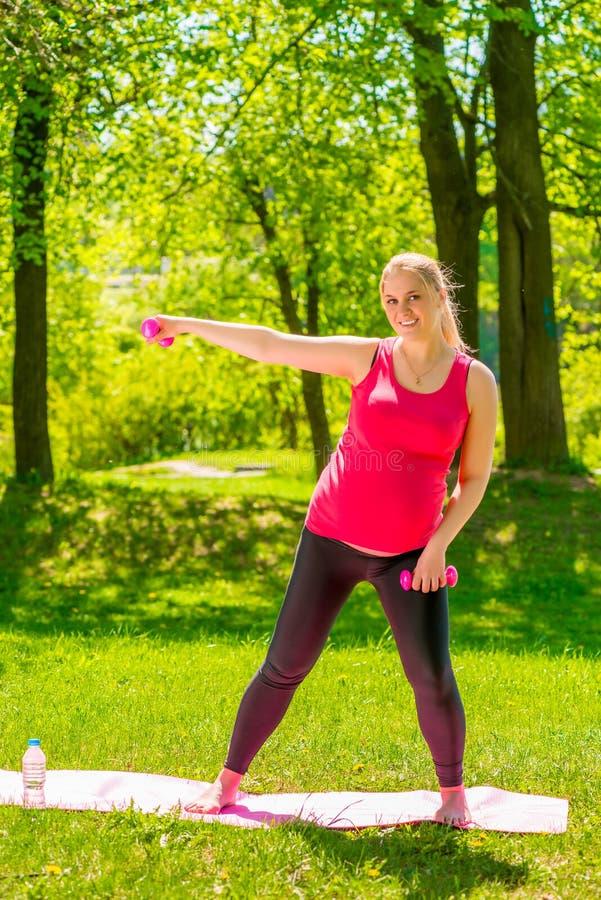 做与哑铃的年轻人孕妇锻炼 免版税库存照片