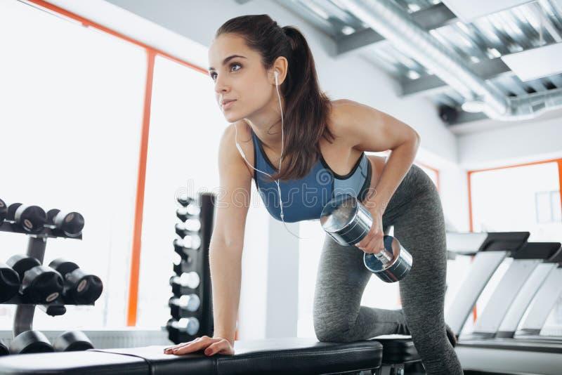 做与哑铃的年轻美丽的妇女锻炼在健身房 免版税库存照片