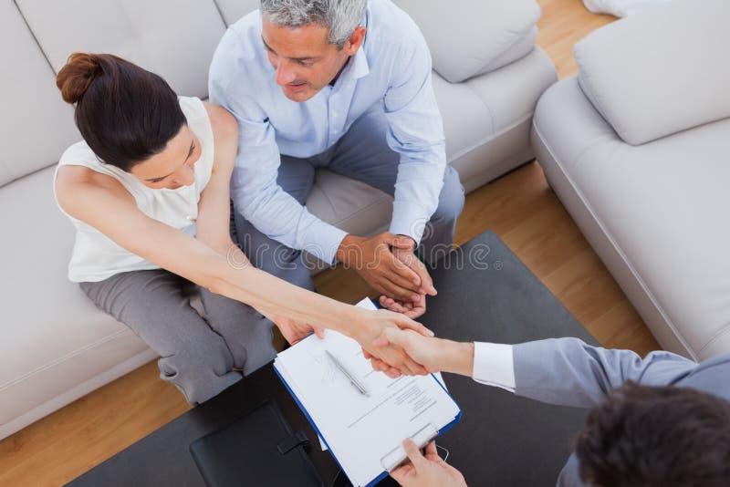 做与商人的女实业家握手坐沙发 库存图片