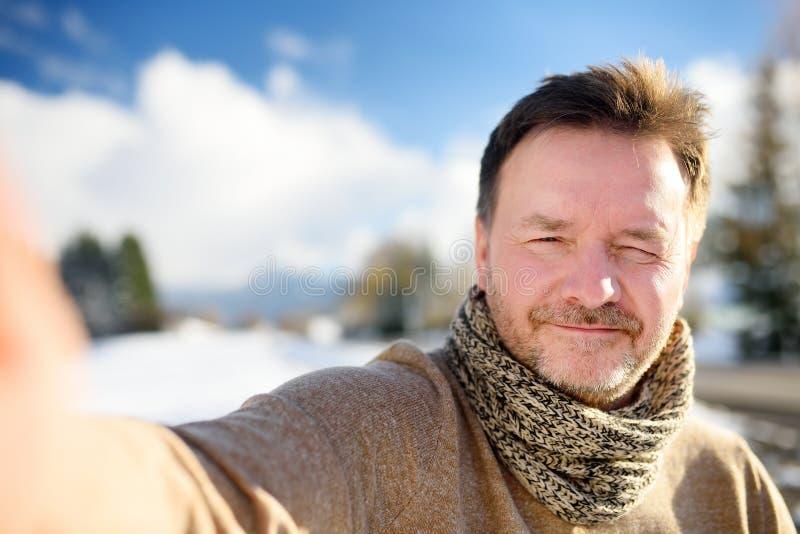 做与多雪的巴法力亚阿尔卑斯的英俊的milddle年龄人一自画象selfie在背景 免版税图库摄影
