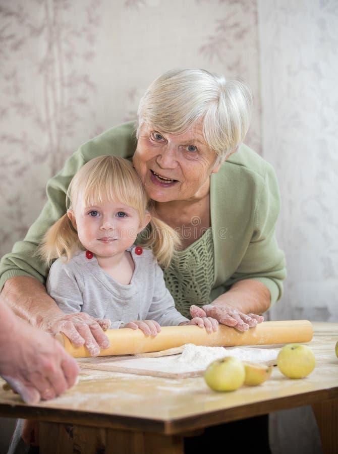 做与女孩的一个老妇人小的饼 看在照相机 库存图片