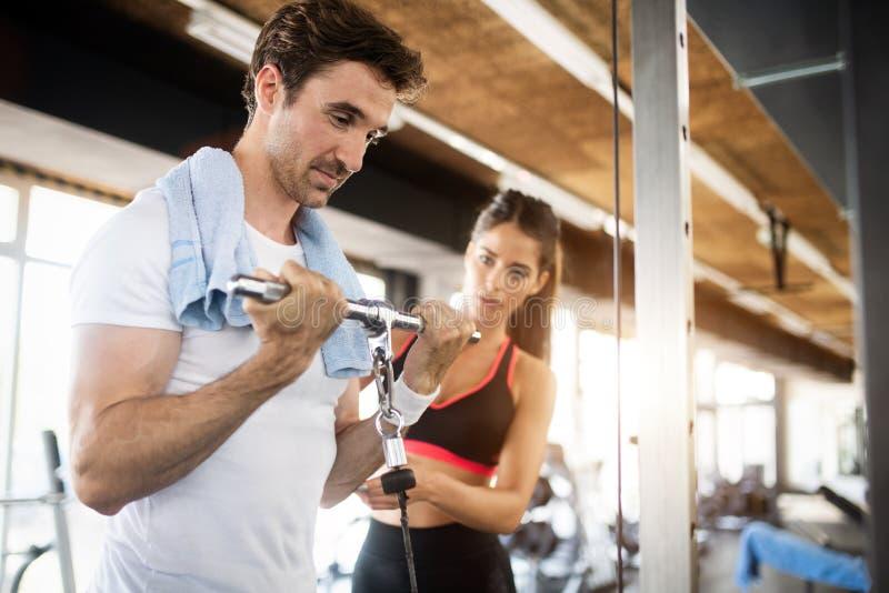 做与她的个人教练员协助的运动的人重量锻炼  免版税库存照片