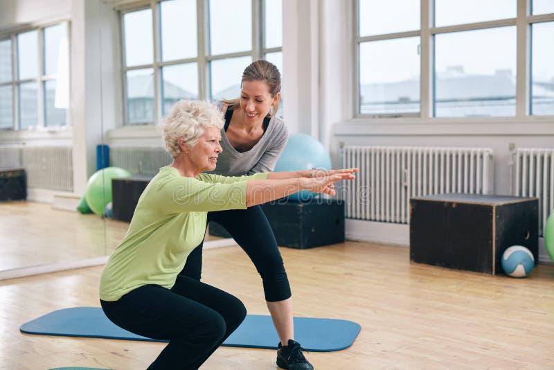做与她的个人教练员的年长妇女锻炼 免版税库存照片