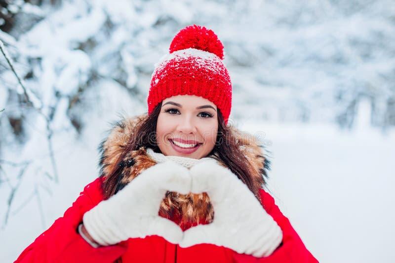 做与她的手指的俏丽的浪漫年轻女人心脏姿态在她的显示她的爱的胸口前面在冬天 免版税库存图片