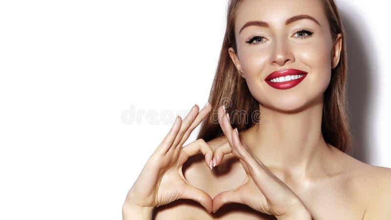 做与她的手指的浪漫少妇心脏形状 爱和情人节标志 有愉快的微笑的时尚女孩 免版税库存照片