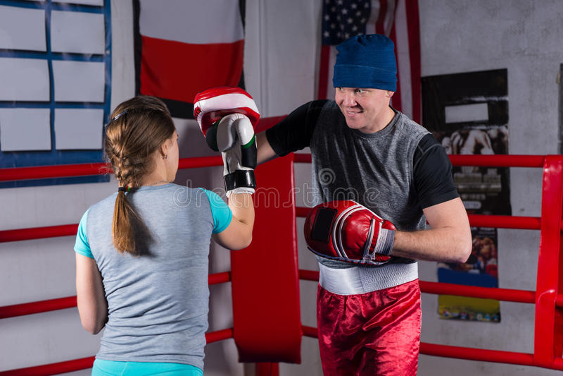 做与她的教练的少妇kickboxing的训练 免版税库存图片