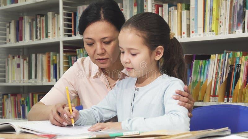 做与她的母亲的逗人喜爱的小女孩家庭作业 免版税库存照片