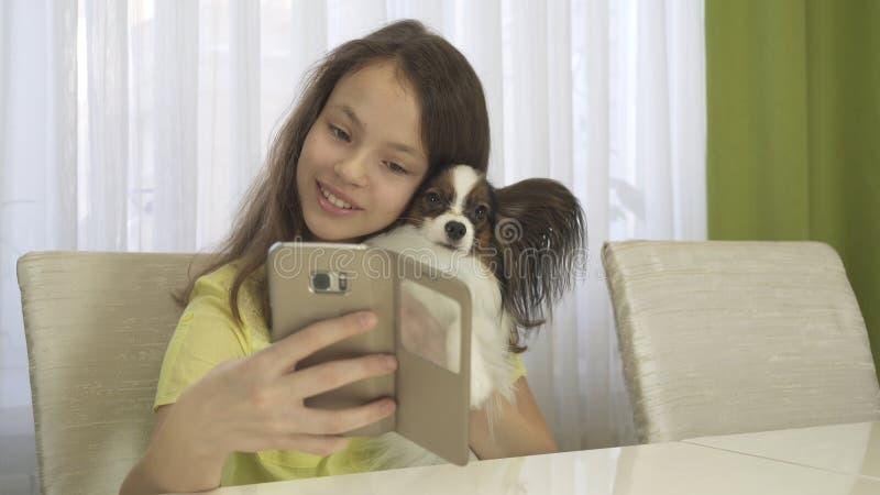 做与她的狗的愉快的十几岁的女孩selfie 库存照片