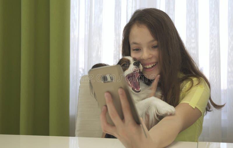 做与她的狗的愉快的十几岁的女孩selfie 库存图片