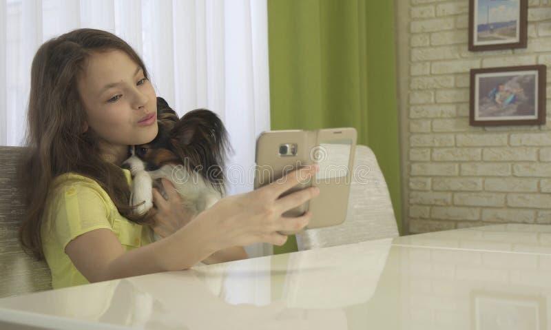做与她的狗的愉快的十几岁的女孩selfie 图库摄影