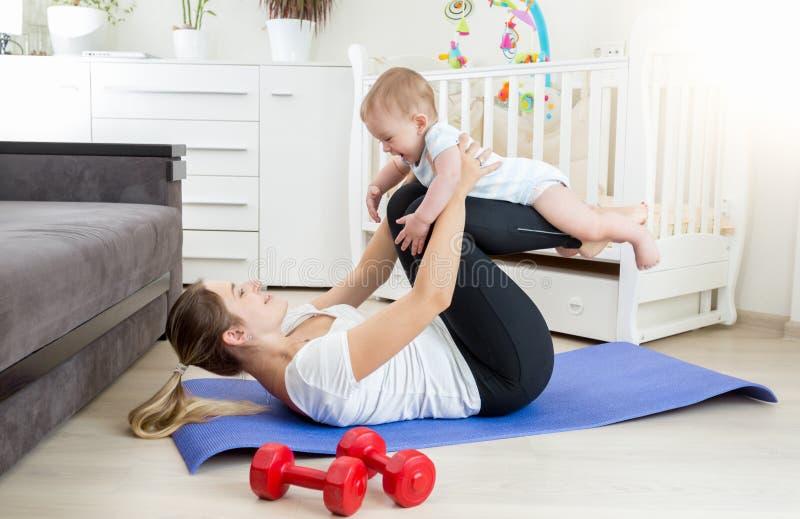 做与她的婴孩的美丽的母亲瑜伽锻炼在地板上在l 免版税库存图片