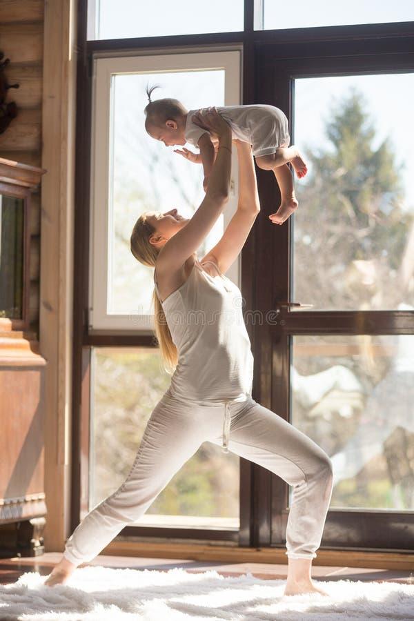做与她的婴孩的年轻可爱的运动的母亲锻炼, ho 免版税库存照片