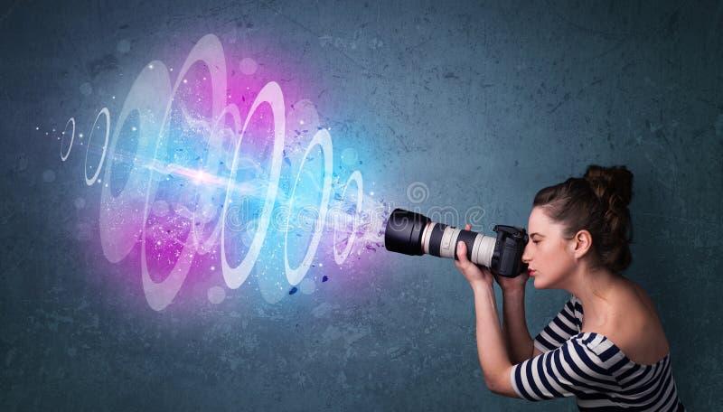 做与强有力的光束的摄影师女孩照片 免版税库存图片