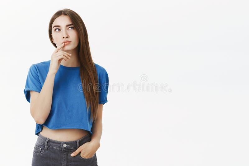 做与手指的时髦蓝色播种的上面的创造性的聪明和体贴的可爱的欧洲妇女姿态  免版税图库摄影