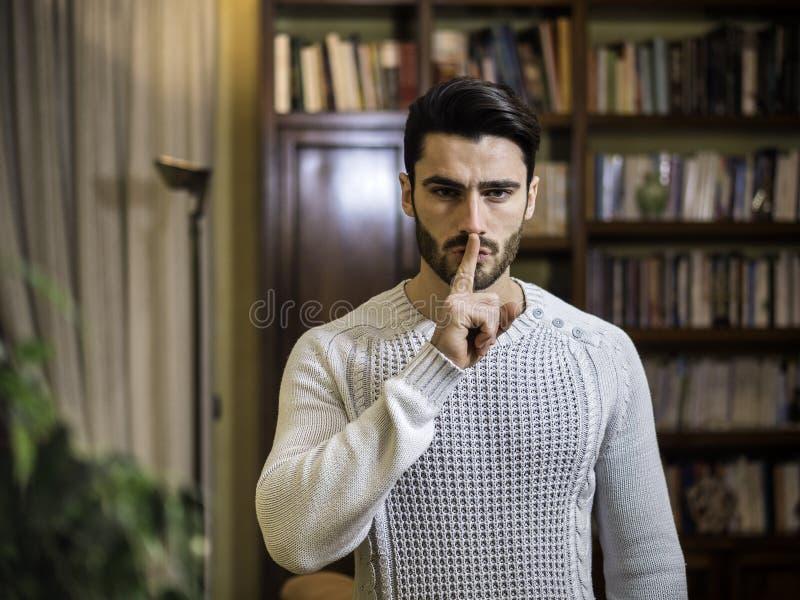 做与手指的英俊的年轻人静寂标志在嘴唇 库存图片
