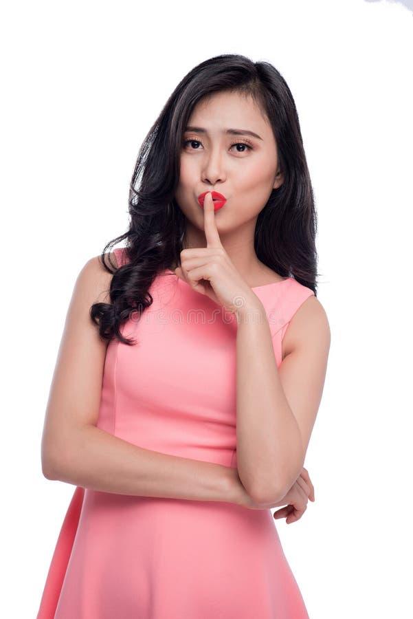 做与手指的年轻俏丽的妇女沈默姿态在嘴唇 图库摄影