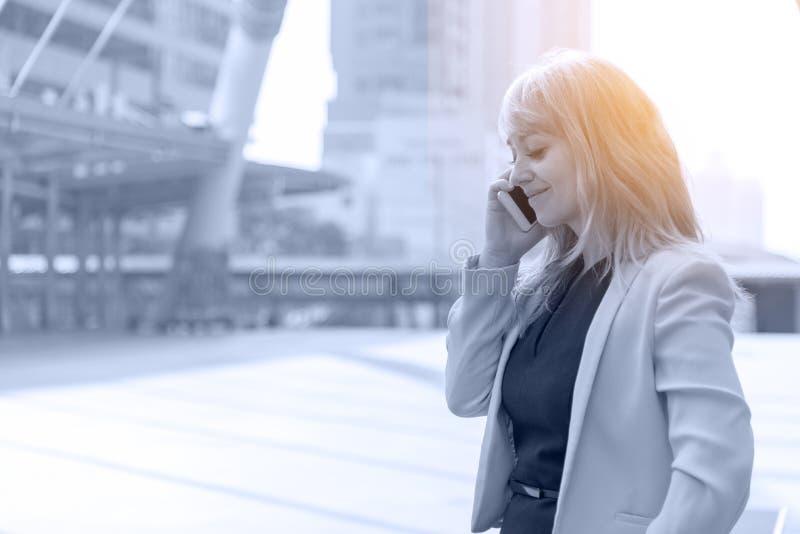 做与手机的女实业家交谈 企业和通信概念 技术和生活方式概念城市和 库存图片