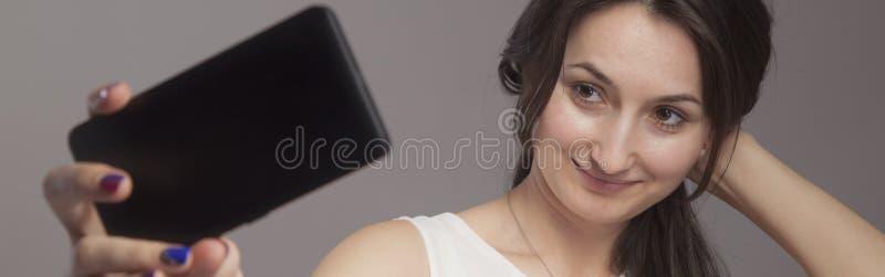 做与手机的妇女画象selphie 爱和正面情感概念 库存图片