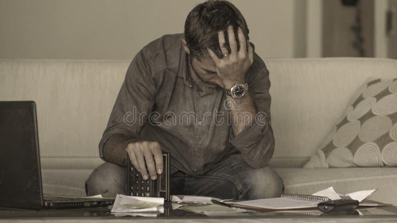 做与文书工作和计算器的年轻在家被注重的和绝望人客厅长沙发国内会计被淹没 免版税图库摄影