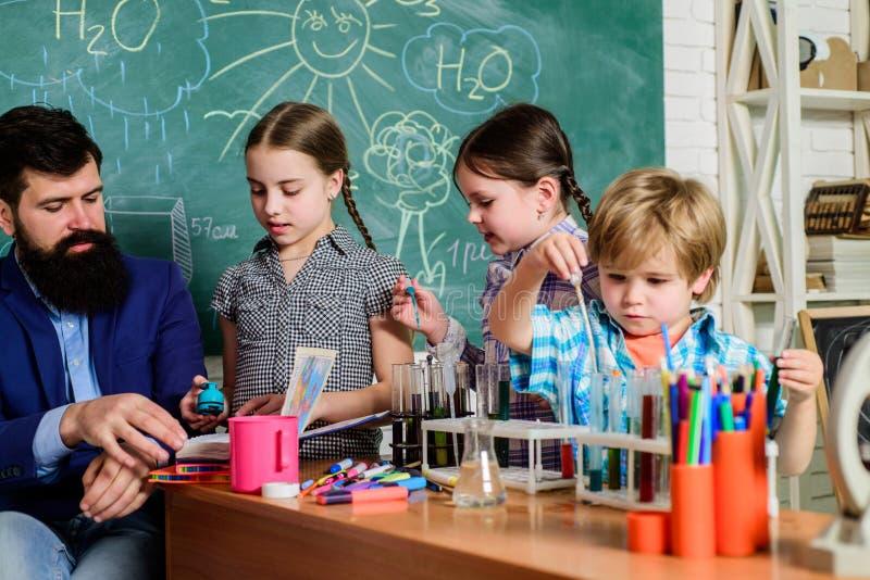 做与显微镜的学生科学实验在实验室 学校学习科学的孩子科学家 E 免版税库存图片