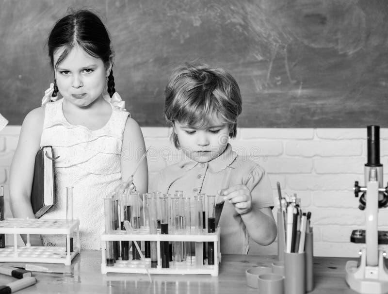 做与显微镜的学生科学实验在实验室 r 学校学习科学的孩子科学家 ?? 免版税库存图片