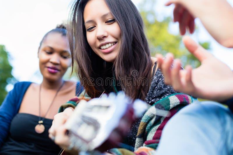 做与朋友的吉他演奏员女孩音乐在公园 库存图片