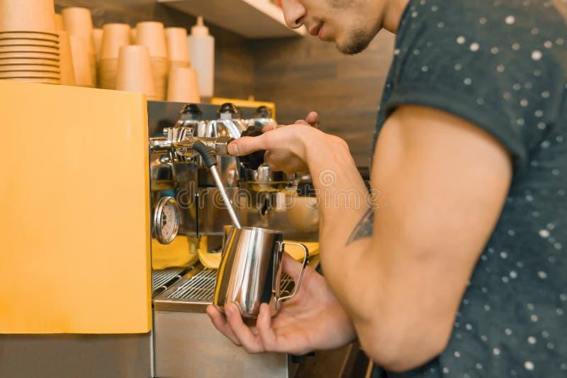 做与机器的年轻男性咖啡馆工作者咖啡 库存照片