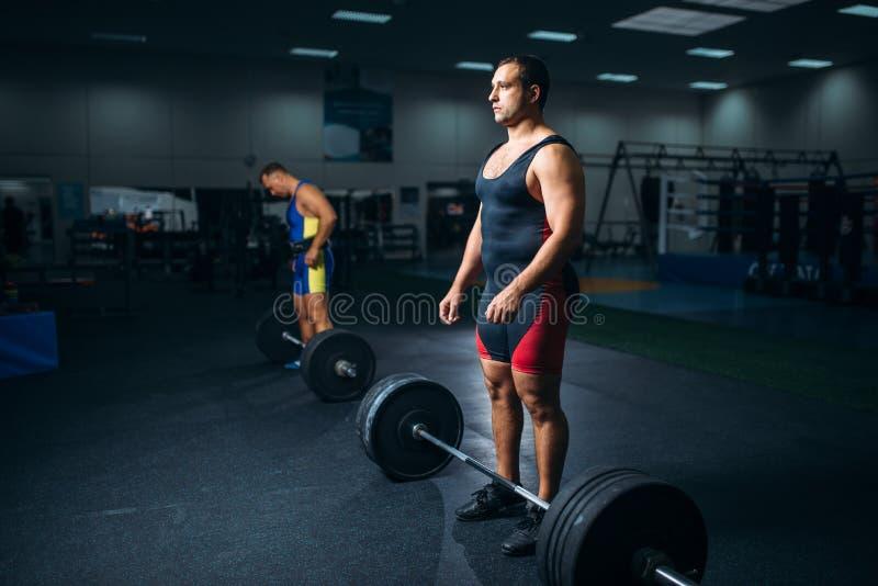 做与杠铃的两个举重运动员锻炼 免版税库存图片