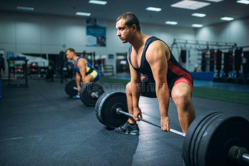 做与杠铃的两个举重运动员锻炼 库存图片