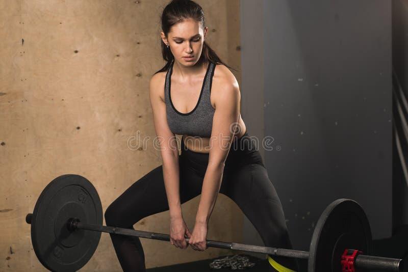 做与杠铃的健身房的肌肉妇女重量级的锻炼 库存图片