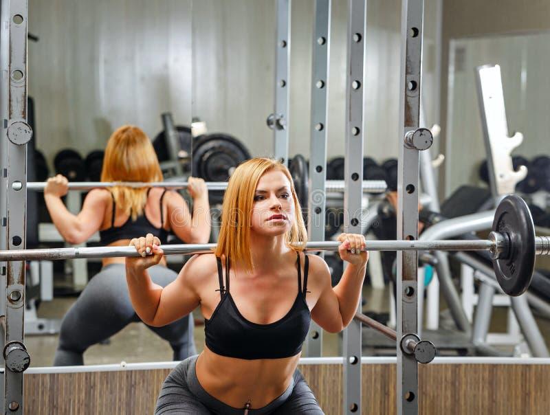 做与杠铃的女孩锻炼在健身房 免版税库存照片