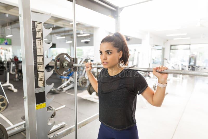 做与杠铃的妇女蹲坐在健身俱乐部 库存照片