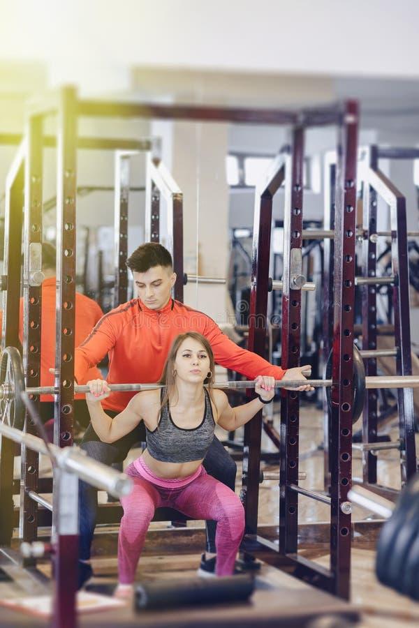 做与杠铃的少女蹲坐在健身房在教练员的监督下 免版税库存图片