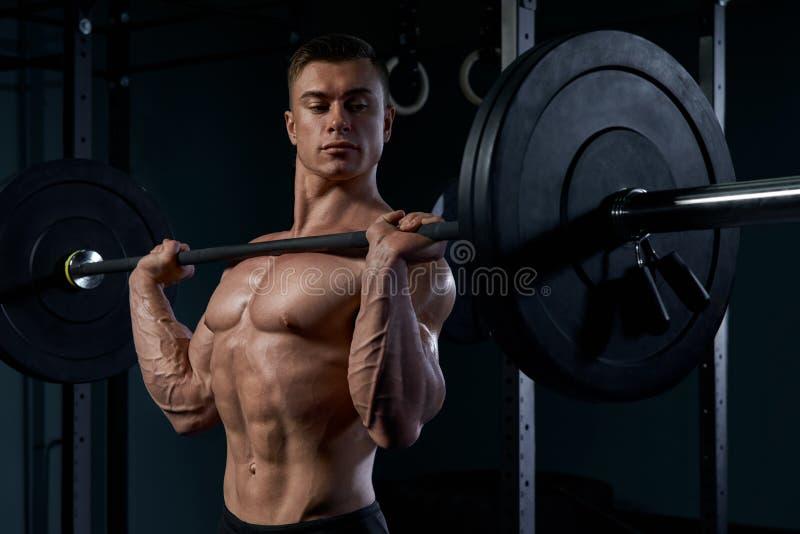 做与杠铃的爱好健美者锻炼在健身房 免版税库存照片