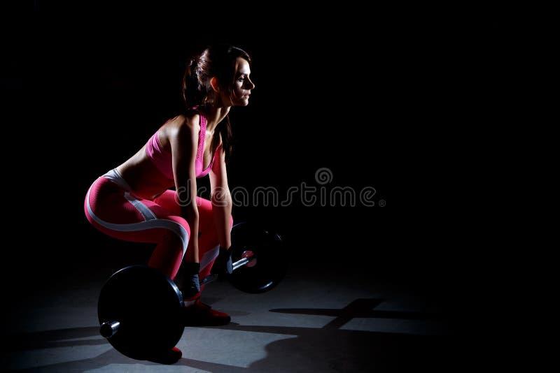 做与杠铃的美丽的健身妇女蹲坐 体育妇女剪影黑背景的 免版税库存照片