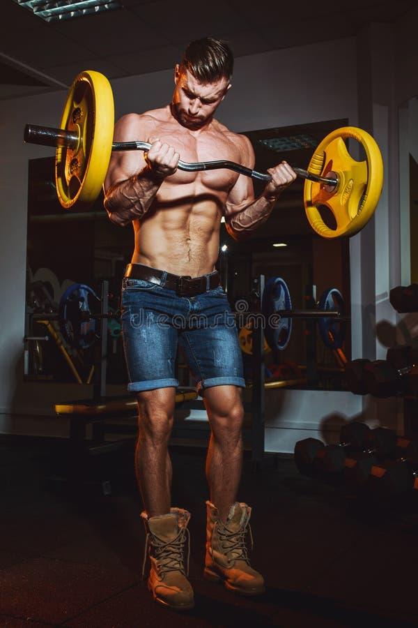 做与杠铃的运动年轻人锻炼在健身房 英俊的肌肉爱好健美者人解决 库存照片
