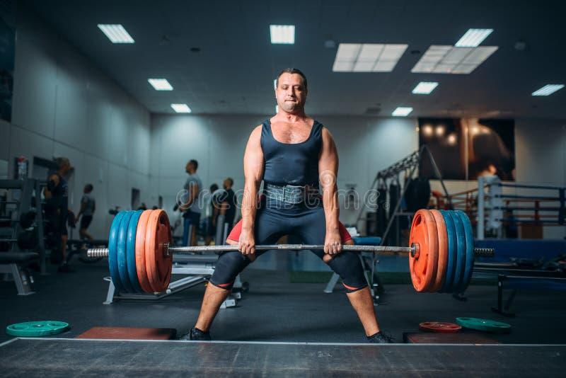 做与杠铃,deadlift的举重运动员锻炼 免版税图库摄影