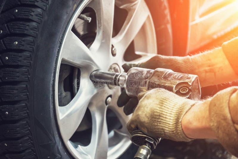 做与气动力学的板钳的汽车修理师工作者轮胎或轮子替换在修理服务站车库  库存照片